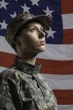 Mujer militar delante de la bandera de los E.E.U.U., mujer militar vertical delante de la bandera de los E.E.U.U., vertical Imagen de archivo