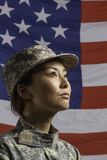 Mujer militar delante de la bandera de los E.E.U.U., mujer militar vertical delante de la bandera de los E.E.U.U., vertical Imágenes de archivo libres de regalías
