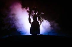 Mujer misteriosa, escena del horror de la mujer asustadiza de la muñeca del fantasma en fondo azul marino con humo Foto de archivo libre de regalías