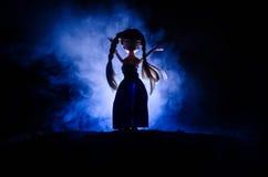 Mujer misteriosa, escena del horror de la mujer asustadiza de la muñeca del fantasma en fondo azul marino con humo Imagen de archivo libre de regalías