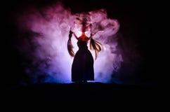 Mujer misteriosa, escena del horror de la mujer asustadiza de la muñeca del fantasma en fondo azul marino con humo Fotos de archivo
