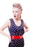 Mujer modela rubia joven divertida en vestido del lunar con la cámara de mirada wonderingly en jarras de los bigudíes en blanco Imagen de archivo libre de regalías