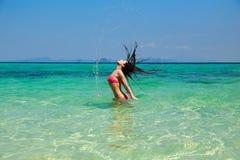Mujer modelo hermosa que salpica su pelo en wate del azul de la turquesa Foto de archivo libre de regalías