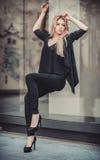 Mujer modelo joven hermosa que presenta en el ambiente de cristal moderno Imágenes de archivo libres de regalías