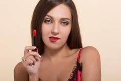 Mujer modelo joven que hace maquillaje en blanco Imagen de archivo libre de regalías