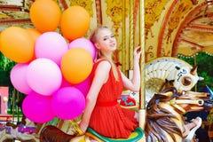 Mujer modelo joven que monta un carrusel Imagenes de archivo