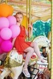 Mujer modelo joven que monta un carrusel Foto de archivo