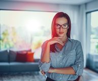 Mujer moderna confiada joven del empollón que presenta en sala de estar en sunse fotos de archivo libres de regalías