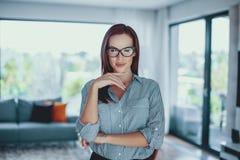 Mujer moderna confiada joven que presenta en sala de estar imagen de archivo