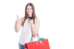 Mujer moderna de las compras que consume el teléfono móvil y el pulgar Imagenes de archivo