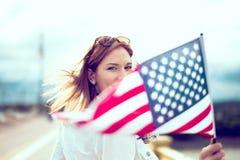 Mujer moderna del patriota joven que lleva a cabo la profundidad de la bandera de los E.E.U.U. del campo imagenes de archivo