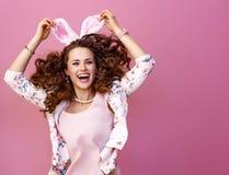 Mujer moderna feliz aislada en el salto rosado del fondo foto de archivo libre de regalías