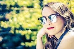 Mujer moderna joven con las gafas de sol y la expresión casual Foto de archivo libre de regalías