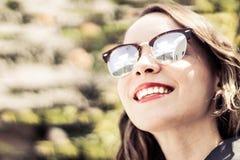 Mujer moderna joven con las gafas de sol y la expresión casual Fotografía de archivo
