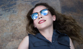 Mujer moderna joven con las gafas de sol y la expresión casual Fotos de archivo