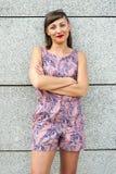 Mujer moderna joven contra la pared en la ciudad que sonríe al camer Imagen de archivo libre de regalías