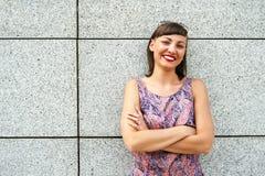 Mujer moderna joven contra la pared en la ciudad que sonríe al camer Imagenes de archivo