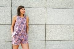 Mujer moderna joven contra la pared en la ciudad que sonríe al camer Imagen de archivo