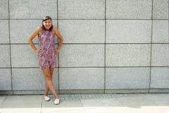 Mujer moderna joven contra la pared en la ciudad que sonríe al camer Fotos de archivo