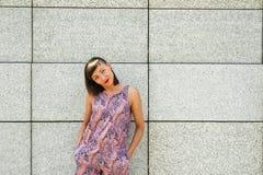 Mujer moderna joven contra la pared en la sonrisa de la ciudad Fotos de archivo libres de regalías
