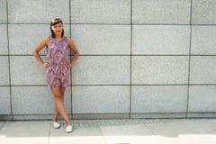 Mujer moderna joven contra la pared en la sonrisa de la ciudad Imágenes de archivo libres de regalías