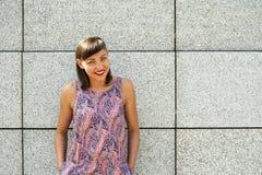 Mujer moderna joven contra la pared en la sonrisa de la ciudad Imagenes de archivo