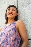 Mujer moderna joven que se opone a la sonrisa de la pared Imagenes de archivo