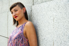Mujer moderna joven que se opone a la sonrisa de la pared Labios rojos a Imágenes de archivo libres de regalías