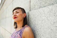 Mujer moderna joven que se opone a la sonrisa de la pared Labios rojos a Imagen de archivo libre de regalías