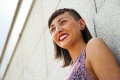 Mujer moderna joven que se opone a la sonrisa de la pared Labios rojos a Imagen de archivo