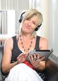 Mujer moderna mayor que pone en sofá con la tableta y el au electrónicos Imágenes de archivo libres de regalías