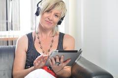 Mujer moderna mayor que pone en sofá con la tableta y el au electrónicos Fotografía de archivo