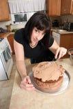 Mujer moderna que hiela la torta Imagen de archivo