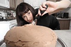 Mujer moderna que hiela la torta Foto de archivo libre de regalías