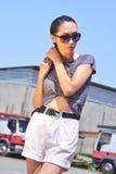 Mujer mojada atractiva preciosa, manos para arriba, pantalones cortos cortos, pelo largo negro y vidrios en los camiones del fond Imagen de archivo libre de regalías