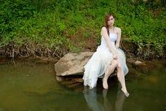Mujer mojada que se sienta en una roca sobre el agua Foto de archivo