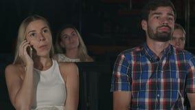Mujer molesta en el teléfono durante película en el cine almacen de metraje de vídeo