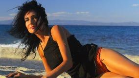 Mujer morena agradable que se relaja en la playa almacen de metraje de vídeo