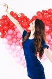 Mujer morena atractiva con los globos y las flores rojos del corazón Imagen de archivo libre de regalías