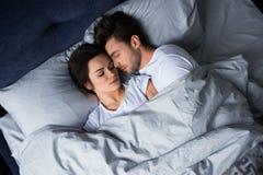 Mujer morena atractiva de abarcamiento del hombre barbudo mientras que duerme Fotografía de archivo libre de regalías