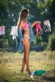 Mujer morena atractiva en el bikini y la camisa que ponen la ropa para secarse en sol Hembra joven sensual con las piernas largas foto de archivo