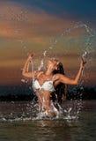 Mujer morena atractiva en el traje de baño blanco mojado que presenta en agua de río con el cielo de la puesta del sol en fondo E Imagenes de archivo