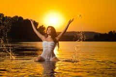 Mujer morena atractiva en la ropa interior blanca mojada que presenta en agua de río con puesta del sol en fondo Hembra joven en  Fotos de archivo