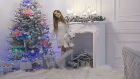 Mujer morena atractiva hermosa que canta cerca del árbol de navidad en casa Año Nuevo y la Navidad almacen de video