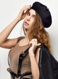 Mujer morena atractiva joven en el sombrero marrón de la boina que mira la esquina foto de archivo libre de regalías