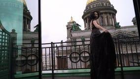 Mujer morena atractiva joven en el vestido de lujo negro que permanece en el balcón en una ciudad metrajes