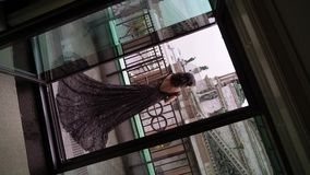 Mujer morena atractiva joven en el vestido de lujo negro que permanece en el balcón en una ciudad almacen de video