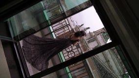 Mujer morena atractiva joven en el vestido de lujo negro que permanece en el balcón en una ciudad almacen de metraje de vídeo