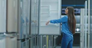 Mujer morena atractiva joven en la camisa para abrir la puerta del refrigerador en la tienda de dispositivos y a comparar con otr