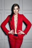 Mujer morena atractiva joven hermosa que lleva diseño elegante de la chaqueta roja y el traje de moda con la joya, zapatos de tac Imagenes de archivo